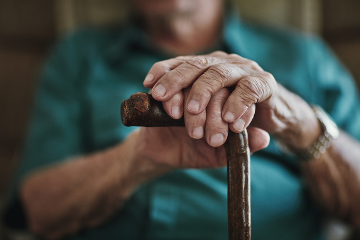 old man's hands resting on the handle of a cane