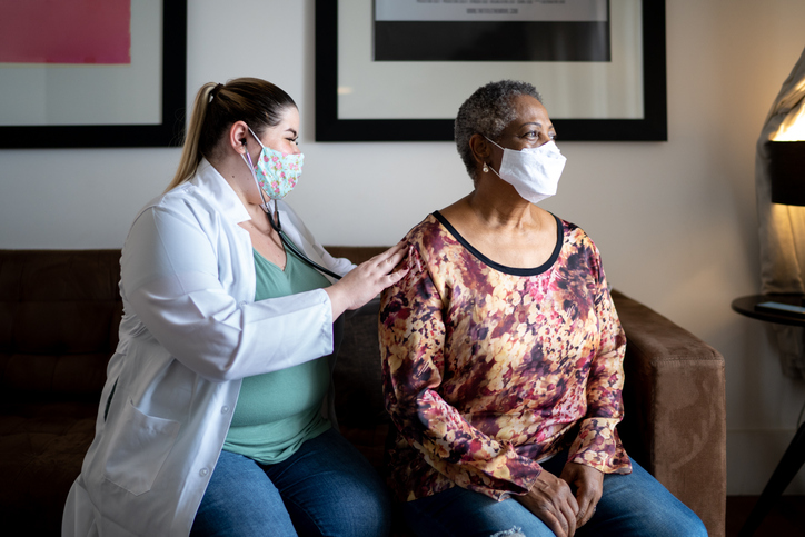 doctor listens to senior patient's breathing, both wearing masks