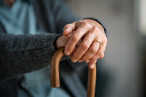 Old woman hands holding walking stick